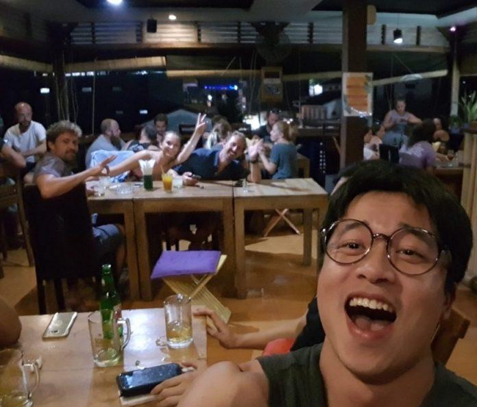 셀카를 찍는 뒷배경의 다른 테이블사람들이 카메라를 보고 v자 포즈를 취하며 환호중