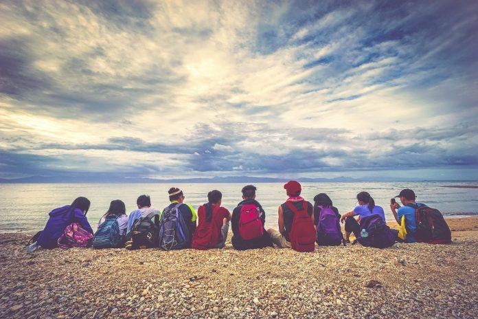 해변가에 앉아 수평선을 바라보는 사람들