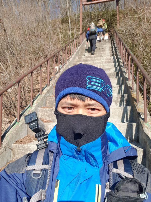 정상으로 올라가는 계단길을 배경으로 찍은 셀카